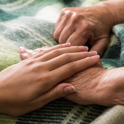 Young Woman's Hand Touching and Holding an Old Woman's Hand